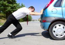 Man pushing car after breakdown