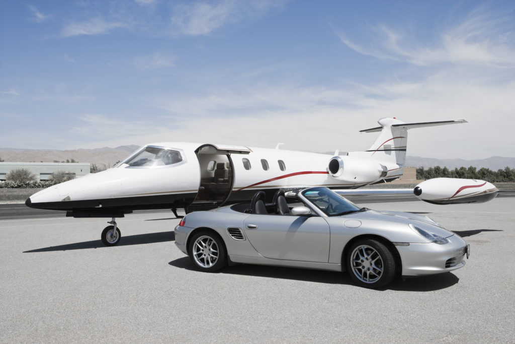 Porsche 911 parked in front of a jet
