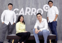 Carro management team in front of Carro logo